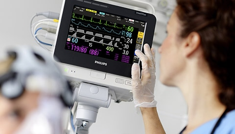 a clinican checking the patient's healthcare parameter on a device